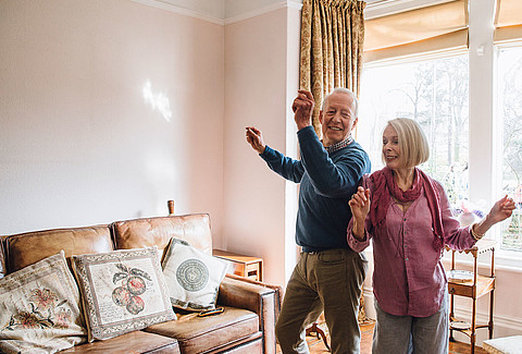 Senioren-Paar tanzt im Eigenheim.