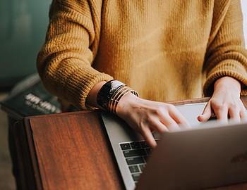Frau mit gelbem Pullover sitzt an Holztisch vor aufgeklapptem Laptop.