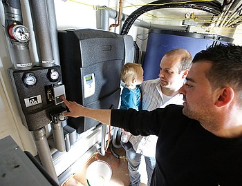 Der Handwerker von Thermondo erklärt Hausbesitzer Thomas Funcke und seinem Sohn Jonathan die Funktionsweise der Heizungspumpe